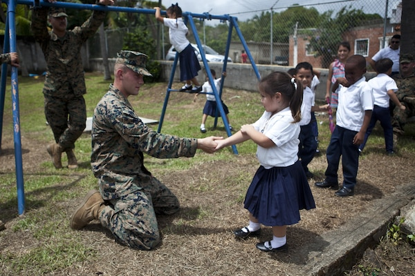 U.S. Marine Lance Cpl. Trai Pelletier, a welder with the Logistics Combat Element, Special Purpose Marine Air-Ground Task Force - Southern Command, greets a child at the ribbon cutting ceremony for the Taufick Bendeck Elementary School in Trujillo, Honduras, July 27, 2017. The Marines are conducting infrastructure improvement projects at local schools in Trujillo at the request of the government of Honduras. The Marines and sailors of SPMAGTF-SC are deployed to Central America to conduct security cooperation training and engineering projects with their counterparts in several Central American and Caribbean nations.