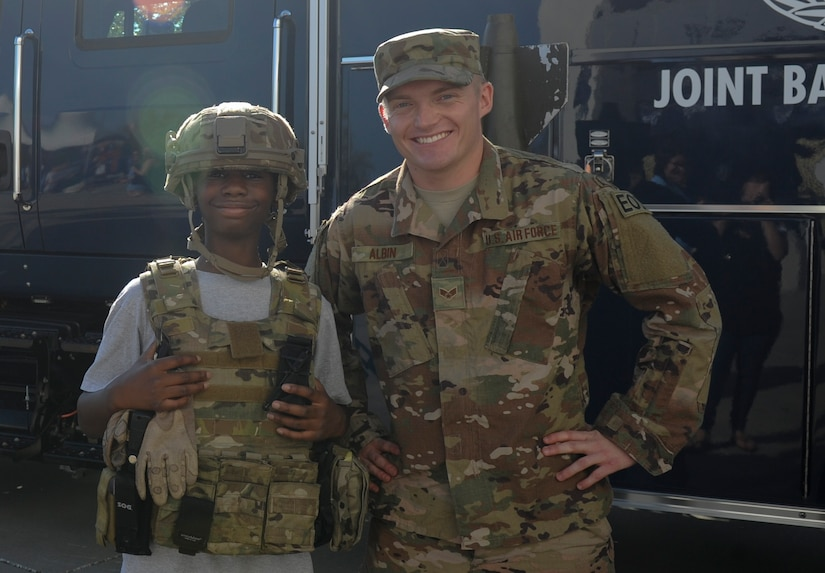 Senior Airman Jonathan Albin, 628th Civil Engineer Squadron Explosive Ordnance Disposal Flight explosive ordnance disposal journeyman, poses for a photo with a member of the Charleston community wearing a helmet and plate carrier vest at the Johnson Hagood Memorial Stadium for the Citadel's Military Appreciation Night, Oct. 14, 2017. Members of the 628th Security Forces Squadron and 437th Airlift Wing represented Joint Base Charleston at the football game. Additionally, the Citadel hosted women's soccer and volleyball games in support of Military Appreciation Week. The Citadel Bulldog's football game against the Wofford Terriers was the capstone event, with Woffard winning 20-16.