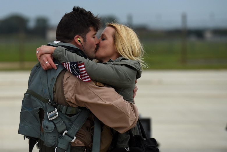 A 492nd Fighter Squadron member greets his wife after returning from a deployment, Oct. 4. F-15E Strike Eagles and Airmen from the 492nd Fighter Squadron and supporting units across the 48th Fighter Wing returned from a six-month deployment to an undisclosed location in Southwest Asia. (U.S. Air Force photo/Airman 1st Class Eli Chevalier)