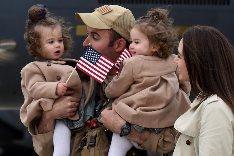 """A 492nd Fighter Squadron member greets his family members after returning from a deployment, Oct. 4. While deployed as the 492nd Expeditionary Fighter Squadron at the 332nd Air Expeditionary Wing, the """"Bolars"""" completed nearly 11,000 flying hours and over 2,000 missions while delivering nearly 4,500 precision-guided munitions in support of U.S. Central Command operations. (U.S. Air Force photo/Airman 1st Class Eli Chevalier)"""