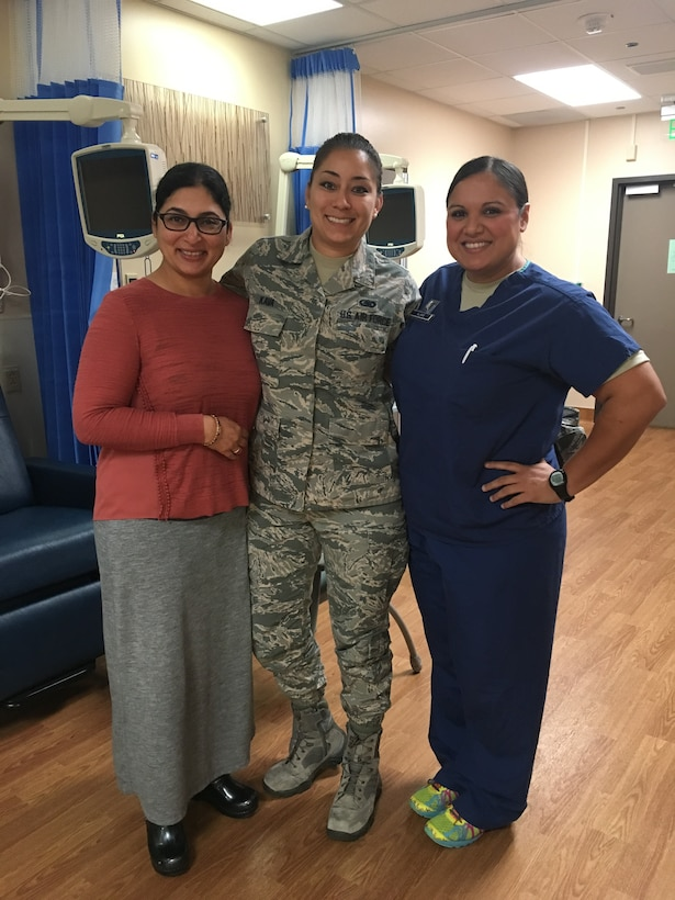 Staff Sergeant Cinnamon Kava (center), 60th Logistics Readiness Squadron unit training manager, poses for a photo Oct. 4 with Dr. Sareena Malhi (left), 60th Medical Operations Squadron physician and Capt. Kendra Alanis (right), 60th MDOS clinical nurse at David Grant USAF Medical Center Oncology unit. Malhi and Alanis were Kava's medical support system during her chemotherapy treatment. (U.S. Air Force photo by Senior Airman Amber Carter)