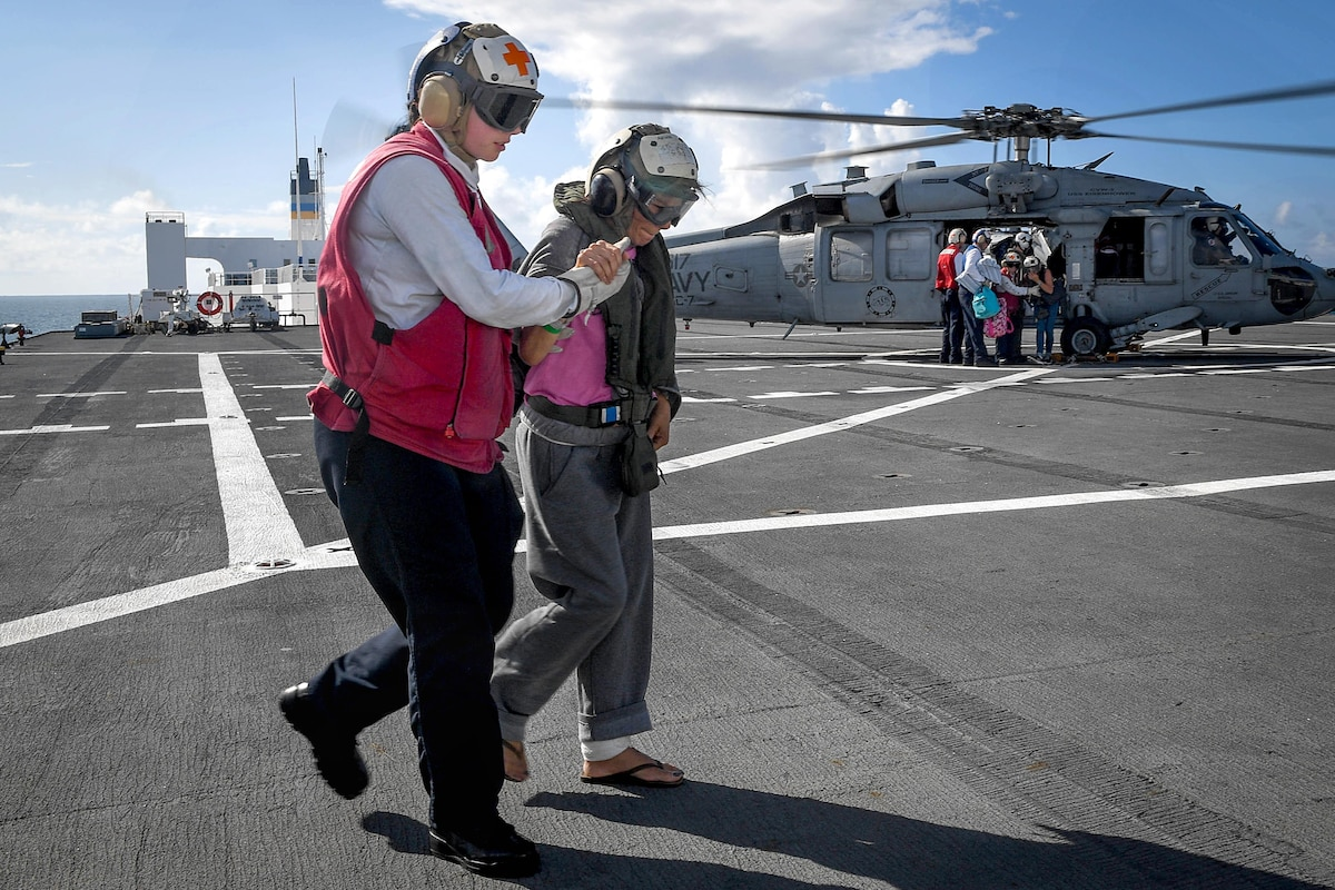A sailor assists a person walking while other sailors help people out of a helicopter.