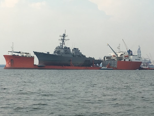 SINGAPORE – (Oct. 7, 2017) – MV Treasure concludes USS John S. McCain (DDG 56) heavy lift operations in the Singapore Strait, Oct. 7. U.S. Navy Supervisor of Salvage and Diving representatives prepared the destroyer for transit to Yokosuka, Japan, later this month.
