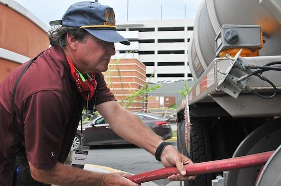 DLA team members pulls a fuel hose