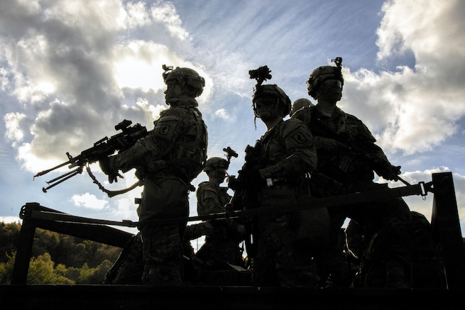 Soldiers, shown in silhouette, stand in a vehicle.