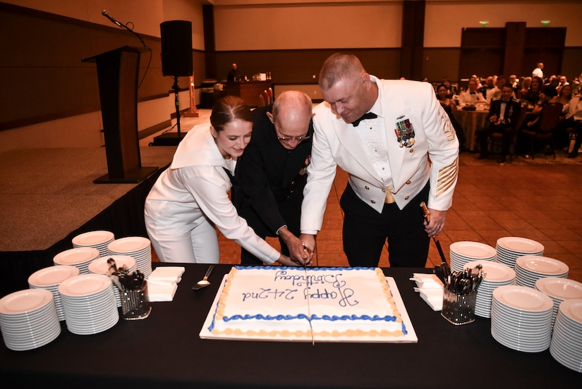 The youngest and oldest Sailor at the Navy's 242nd birthday ball cut the cake with Naval Support Activity Command Master Chief Asa Worcester, Oct. 14, 2017.