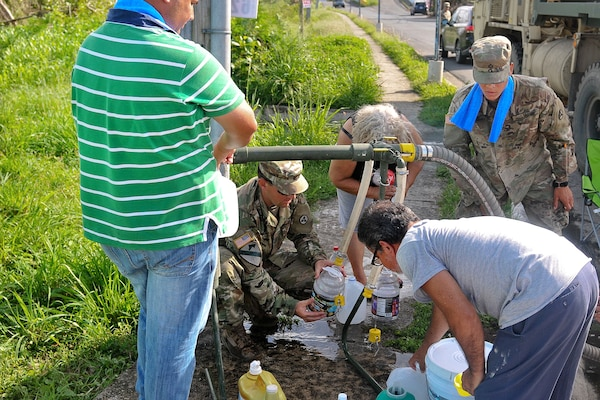 Soldiers and residents gather water from a pipe.