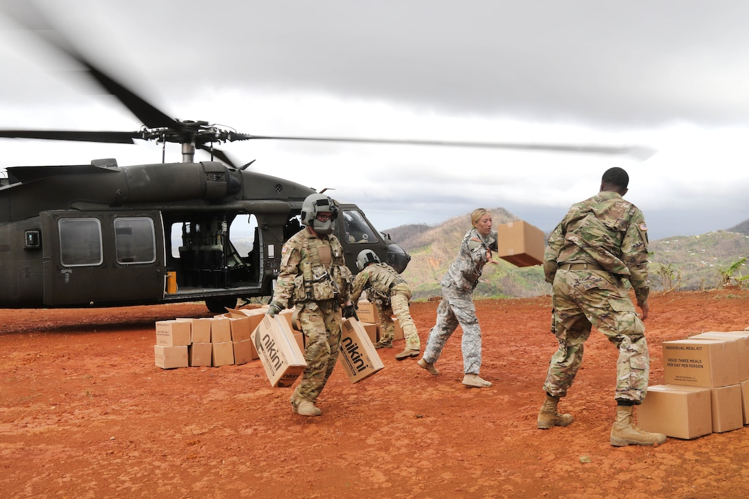 Soldiers move boxes into a pile near a helicopter.