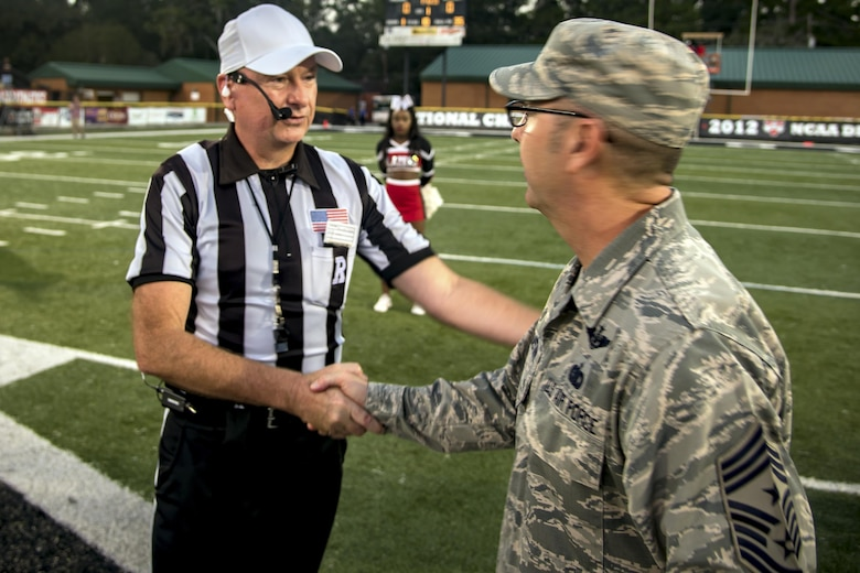 Chief Master Sgt. Jarrod Sebastian, 23d Wing command chief, receives a coin from Michael Lester, college football referee, prior to a military appreciation day game, Oct. 15, 2017, in Valdosta, Ga. Active-duty and retired military members received free admission into the game as appreciation for their service. (U.S. Air Force photo by Airman Eugene Oliver)