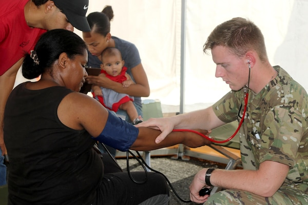 Army Pfc. Leon Good, a medic with the 1st Armored Division, tends to patients near Fajardo, Puerto Rico at the Federal Emergency Management Agency's National Disaster Medical System, a mobile emergency and clinical care facility, Oct. 13, 2017. The medics were seeing up to 150 patients a day. Army photo by Capt. Tyson Friar