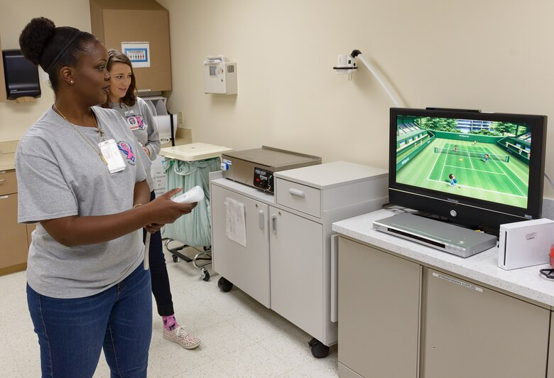 Senior Airman Alishia Loper and Staff Sgt. Leanne Kirk, 81st Medical Group education and training medical administration, test their range of motion using video game console at the Physical and Occupational Therapy clinic open house Oct. 13, 2017, on Keesler Air Force Base, Mississippi. The event was held in celebration of National Physical Therapy and Chiropractic Month and housed several demonstrations to include dry needling, anti-gravity treadmill and power lifting techniques. (U.S. Air Force photo by Andre' Askew)