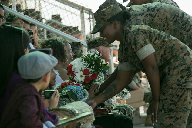 Marines present flowers to the family of  Sgt. Maj. Avery Crespin, former Headquarters Battalion sergeant major, during his retirement ceremony at Lance Cpl. Torrey L. Gray field aboard the Combat Center, September 29, 2017. Crespin served in more than five units and Military Occupational Specialties in his 22 years of active duty service. (U.S. Marine Corps photo by Lance Cpl. Isaac Cantrell)