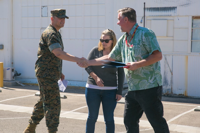 Lt. Cmdr. Juan Chavira, public works officer, Public Works Division, presents time-in-service awards to Glenn Grubbs and Kelley Vendecoevering, workers with PWD, at the PWD Compound aboard the Marine Corps Air Ground Combat Center, Twentynine Palms, Calif., October 10, 2017. Grubbs and Vendecoevering received the awards for dedicating 10 years of service to PWD. (U.S. Marine Corps photo by Lance Cpl. Isaac Cantrell)