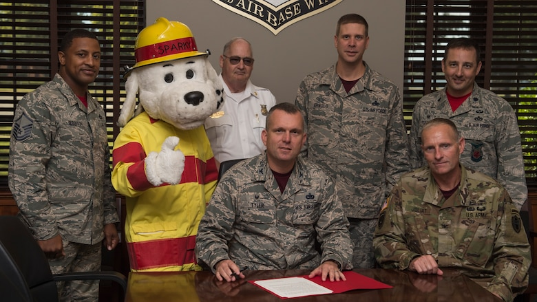 Center, U.S. Air Force Col. Sean Tyler, 633rd Air Base Wing commander, signs the Fire Prevention Week proclamation in the presence of senior leadership at Joint Base Langley-Eustis, Va., Oct. 6, 2017.