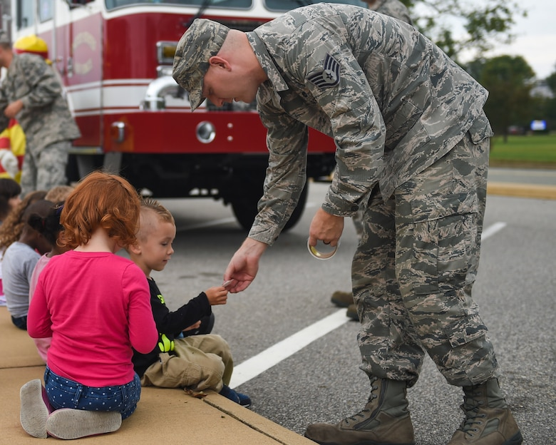 U.S. Air Force Staff Sgt. Corey Watkins, 633rd Civil Engineer Squadron firefighter crew chief, hands stickers to children from the Child Development Center at Joint Base Langley-Eustis, Va., Oct. 10, 2017.
