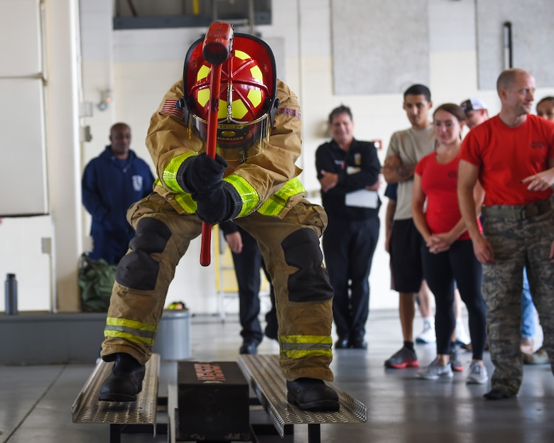 A U.S. Air Force Airman moves a weight with a sledgehammer during the Fire Prevention Week Firefighter's Combat Challenge at Joint Base Langley-Eustis, Va., Oct. 13, 2017.