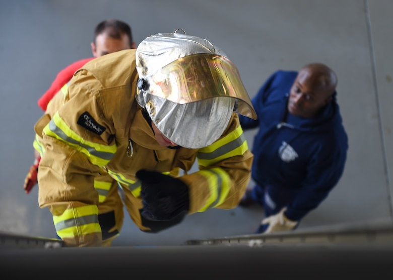 A U.S. Air Force Airman climbs a ladder during the Fire Prevention Week Firefighter's Combat Challenge at Joint Base Langley-Eustis, Va., Oct. 13, 2017.