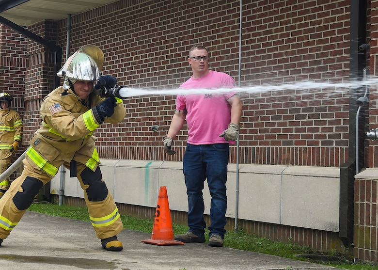 A U.S. Air Force Airman sprays water during the Fire Prevention Week Firefighter's Combat Challenge at Joint Base Langley-Eustis, Va., Oct. 13, 2017.