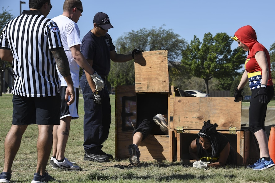 The 17th Training Wing Public Affairs team cheer each other on while completing an obstacle course during the Fire Muster Challenge beside the Fire Department on Goodfellow Air Force Base, Texas Oct. 13, 2017. The course was set up to simulate maneuvering though dark and confined areas. (U.S. Air Force photo by Airman 1st Class Zachary Chapman/Released)