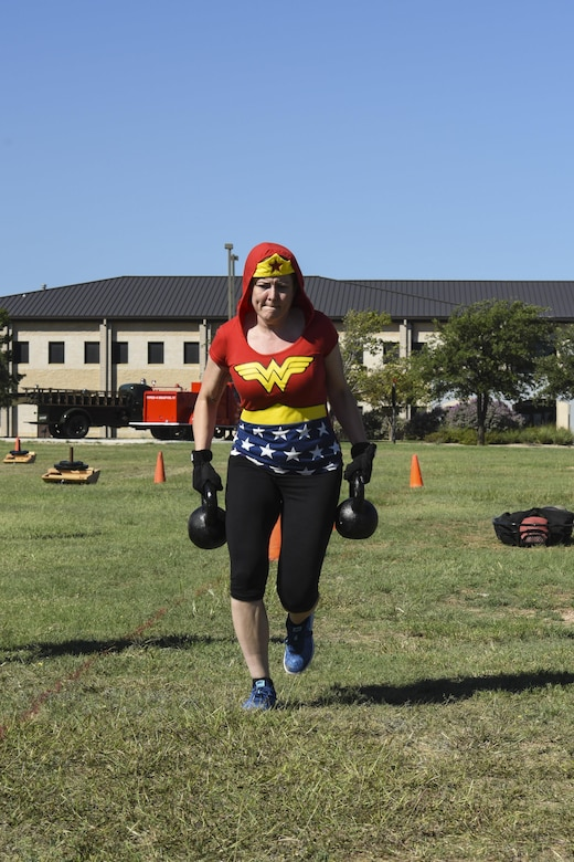 Master Sgt. Joy Meek, 17th Training Wing Public Affairs superintendent, races to the finish of the kettle bell segment of the Fire Muster Challenge beside the Fire Department on Goodfellow Air Force Base, Texas Oct. 13, 2017. Each member of the teams had to carry the kettle bells back and forth within the designated area. (U.S. Air Force photo by Airman 1st Class Zachary Chapman/Released)