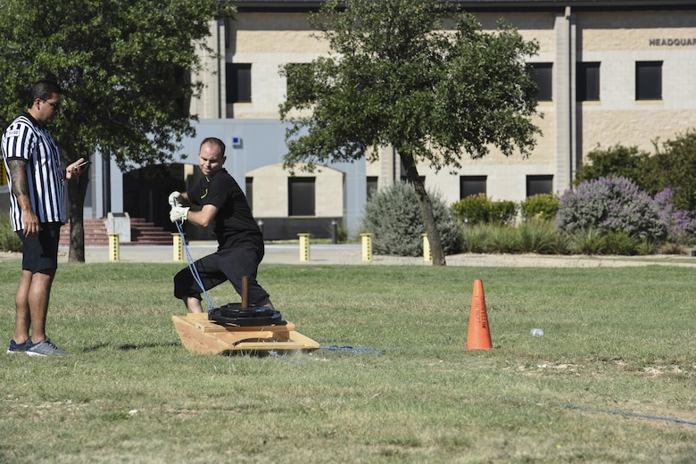 James Orlando, 17th Training Wing Public Affairs visual information specialist, pulls a sled of weights during the Fire Muster Challenge beside the Fire Department on Goodfellow Air Force Base, Texas Oct. 13, 2017. The Fire Muster Challenge tested a team's strength and ability to work together. (U.S. Air Force photo by Airman 1st Class Zachary Chapman/Released)