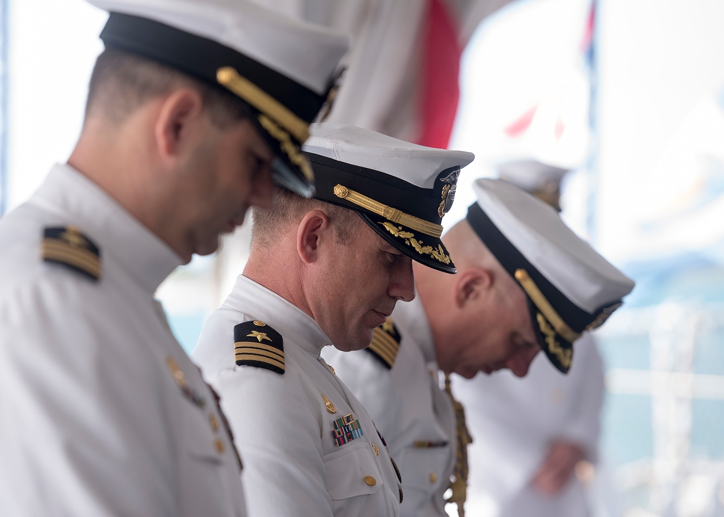 The official party bow for the invocation during the Naval Submarine Support Command (NSSC) Pearl Harbor change of command ceremony aboard the Battleship Missouri Memorial in Pearl Harbor, Hawaii.   (U.S. Navy photo by Mass Communication Specialist 2nd Class Michael Lee/Released)