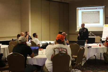 Colonel David Fallon, the 9th Marine Corps District commanding officer, speaks with wrestling coaches during the National Wrestling Coaches Association's Leadership Academy in Salina, Kan., Oct. 6. Fallon spoke to coaches about the traits between Marines and wrestlers share. In November 2016, the Marine Corps expanded its marketing efforts into the wrestling world to locate and recruit men and women who the Marine Corps believes will be successful in all military occupational specialties. (Official U.S. Marine photo by Sgt. Francisco Martinez)