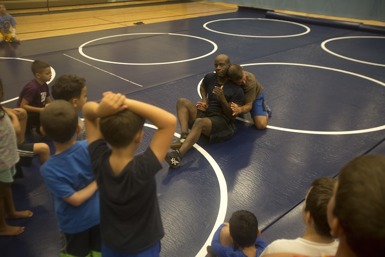 Retired Master Gunnery Sgt. Gus Alexander, the head coach of Marine Corps Base Hawaii's youth wrestling team, leads wrestlers in warm-ups during a practice at the Youth Semper Fit Center, Oct. 12, 2017. The program, organized by Marine Corps Community Services, works in conjunction with Police Activities League and USA Wrestling to arrange wrestling tournaments with competitors from across the island of Oahu. (U.S. Marine Corps photo by Lance Cpl. Luke Kuennen)
