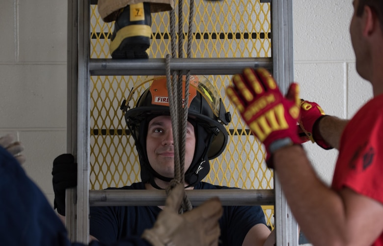 U.S. Air Force Airman 1st Class Zachariah Christenson, Firefighter Combat Challenge safety monitor, stabilizes a ladder climb obstacle during the challenge at Joint Base Langley-Eustis, Va., Oct. 13, 2017.