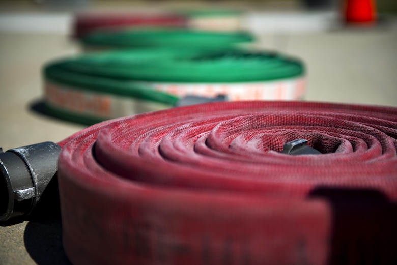 Fire hoses rest on the ground during the 2017 Fire Prevention Week Fire Muster, Oct. 13, 2017, at Moody Air Force Base, Ga. The 23d Civil Engineer Squadron fire department designed the muster to allow teams of Airmen to compete in several events, ranging from a hose roll to a fire truck pull. Event organizers wanted Airmen to experience being a firefighter in a way that got people active. (U.S. Air Force photo by Airman 1st Class Erick Requadt)