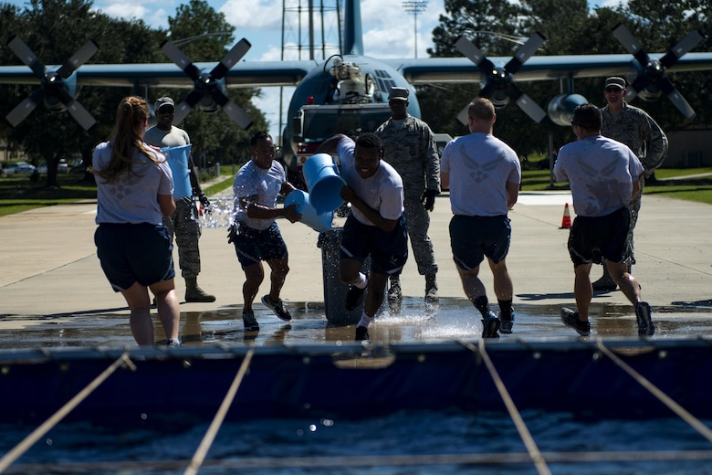 """Airmen assigned to the 23d Security Force Squadron run to fill a trash can with water in the """"bucket brigade"""" event during the 2017 Fire Prevention Week Fire Muster, Oct. 13, 2017, at Moody Air Force Base, Ga. The 23d Civil Engineer Squadron fire department designed the muster to allow teams of Airmen to compete in several events, ranging from a hose roll to a fire truck pull. Event organizers wanted Airmen to experience being a firefighter in a way that got people active. (U.S. Air Force photo by Airman 1st Class Erick Requadt)"""