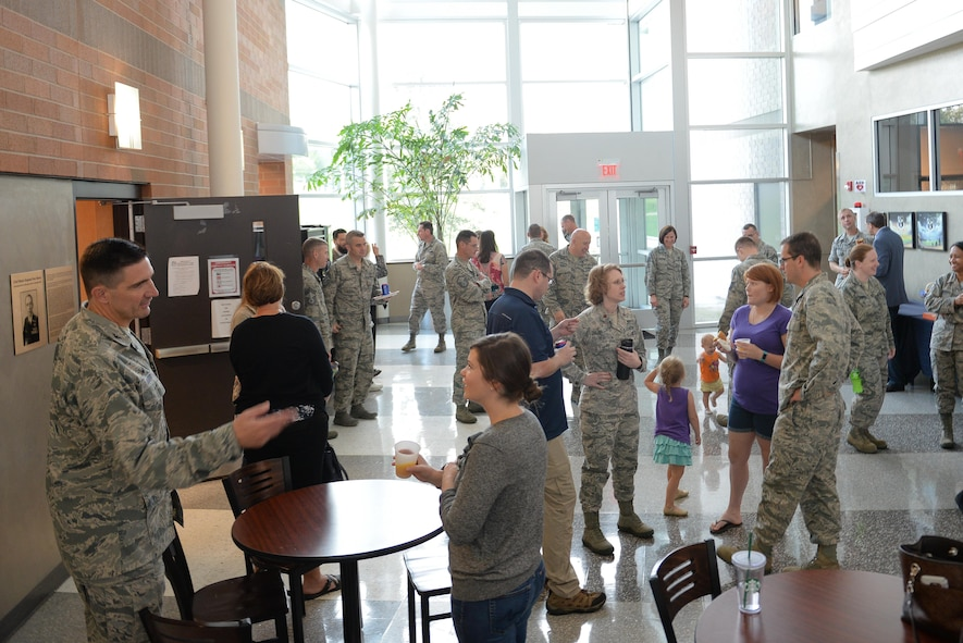 Service members and spouses mingle together at the Spouses' Event held by the 557th Weather Wing at Offutt Air Force Base, Nebraska, Oct. 3, 2017. The event was designed to give spouses a deeper understanding of the weather mission.