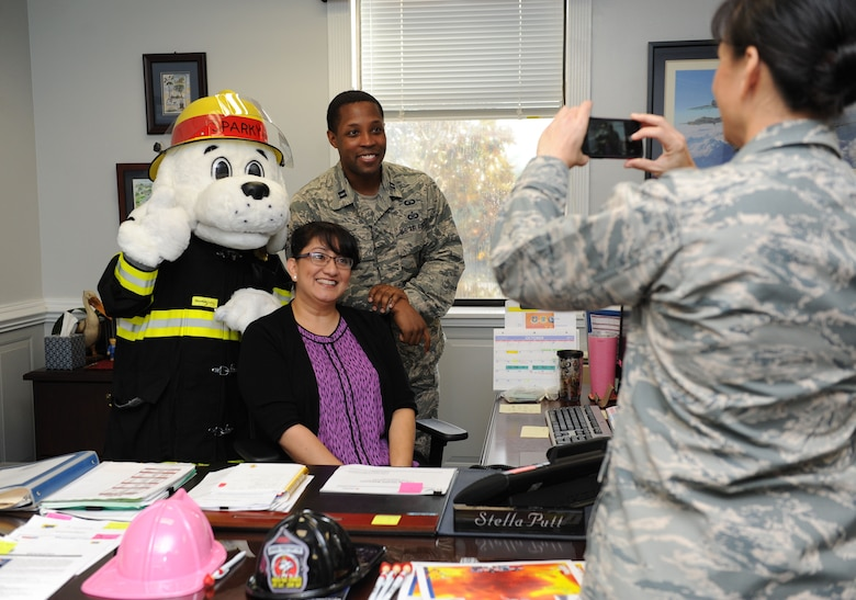 Col. Debra Lovette, 81st Training Wing commander, takes a photo of her staff with Sparky the Fire Dog at the 81st TRW headquarters building during Fire Prevention Week kick off Oct. 10, 2017, on Keesler Air Force Base, Mississippi. The week-long event includes fire drills, literature handouts, stove fire demonstrations around the base and concludes with an open house at the fire department Oct. 14. (U.S. Air Force photo by Kemberly Groue)