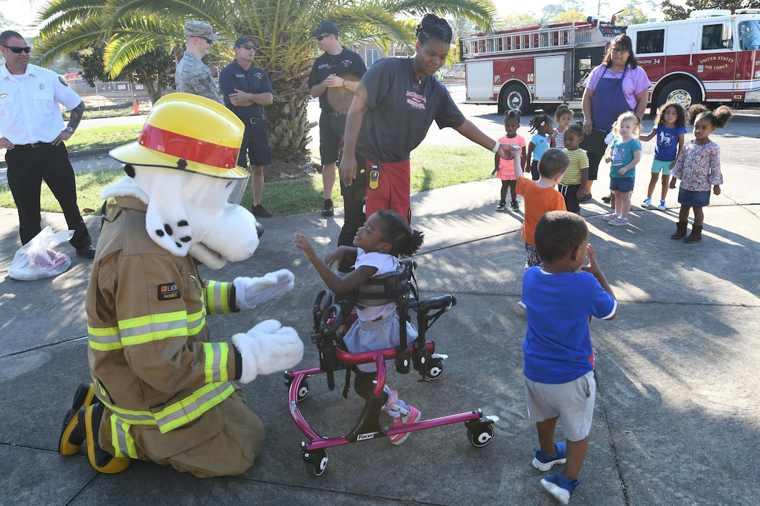 Keesler Child Development Center children meet Sparky the Fire Dog during a Fire Prevention Week demonstration at the CDC Oct. 11, 2017, on Keesler Air Force Base, Mississippi. The week-long event included fire drills, literature handouts, stove fire demonstrations around the base and concluded with an open house at the fire department. (U.S. Air Force photo by Kemberly Groue)