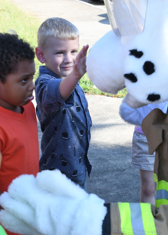 Alexandru Kemayou, son of Airman 1st Class Guy Alein Kemayou, 81st Communications Squadron client systems technician, and Nate Heiney, son of Staff Sgt. Heather Heiney, 403rd Wing public affairs specialist, visit with Sparky the Fire Dog at the Keesler Child Development Center during a Fire Prevention Week demonstration Oct. 11, 2017, on Keesler Air Force Base, Mississippi. The week-long event included fire drills, literature handouts, stove fire demonstrations around the base and concluded with an open house at the fire department. (U.S. Air Force photo by Kemberly Groue)