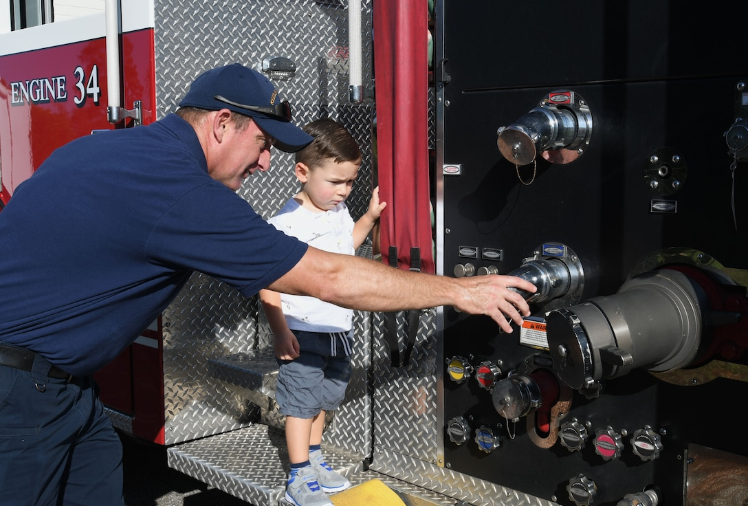 Guy Chadwick, 81st Infrastructure Division firefighter, shows parts of a firetruck to Peter Walker, son of Maj. Sam Walker, 81st Operations Support Flight commander, during a Fire Prevention Week demonstration at the Keesler Child Development Center Oct. 11, 2017, on Keesler Air Force Base, Mississippi. The week-long event included fire drills, literature handouts, stove fire demonstrations around the base and concluded with an open house at the fire department. (U.S. Air Force photo by Kemberly Groue)