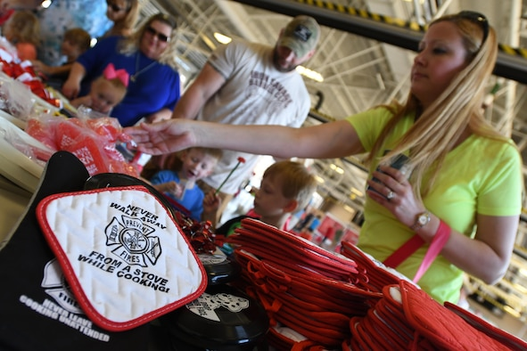 Keesler families collect gifts during the Keesler Fire Department open house at the fire station Oct. 14, 2017, on Keesler Air Force Base, Mississippi. The open house was the concluding event to Fire Prevention Week. Throughout the week the Keesler Fire Department conducted random fire drills, toured various facilities with Sparky the Fire Dog, passed out fire safety information and fire hats for children and provided stove and fire extinguisher demonstrations. (U.S. Air Force photo by Kemberly Groue)