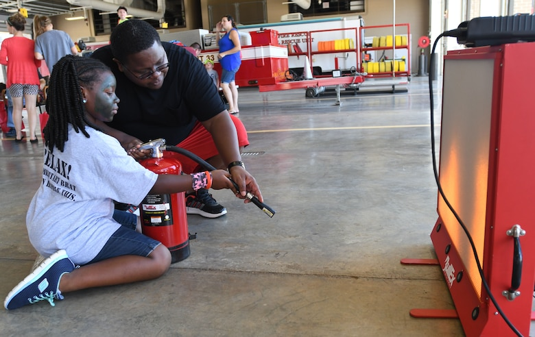 Alketoe and his daughter, Kori, family of Senior Master Sgt. Tiffany Patterson, 81st Force Support Squadron career assistance advisor, demonstrates how to use a fire extinguisher during the Keesler Fire Department open house at the fire station Oct. 14, 2017, on Keesler Air Force Base, Mississippi. The open house was the concluding event to Fire Prevention Week. Throughout the week the Keesler Fire Department conducted random fire drills, toured various facilities with Sparky the Fire Dog, passed out fire safety information and fire hats for children and provided stove and fire extinguisher demonstrations. (U.S. Air Force photo by Kemberly Groue)