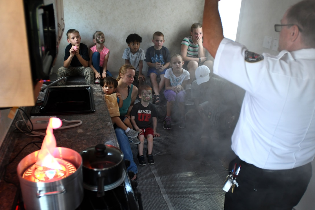 James Shirah, 81st Infrastructure Division fire inspector, shows Keesler children what to do when smoke fills a room at the Keesler Fire Department open house at the fire station Oct. 14, 2017, on Keesler Air Force Base, Mississippi. The open house was the concluding event to Fire Prevention Week. Throughout the week the Keesler Fire Department conducted random fire drills, toured various facilities with Sparky the Fire Dog, passed out fire safety information and fire hats for children and provided stove and fire extinguisher demonstrations. (U.S. Air Force photo by Kemberly Groue)