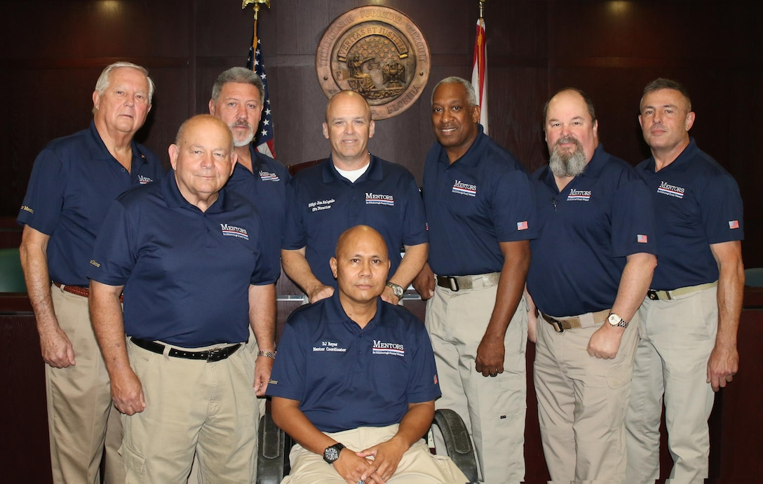 Senior Master Sgt. James Salgado (center, standing) and retired U.S. Army Col. D.J. Reyes (center, seated) with their team of Veterans Treatment Court mentors.