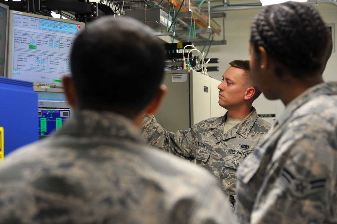 U.S. Air Force Senior Airman Brendan Milligan, 20th Operations Support Squadron (OSS) ground radar systems technician, center, checks radar parameter values at a monitor and a Digital Airport Surveillance Radar control screen as Airman 1st Class Darricka Sides, 20th OSS airfield systems technician, right, and Staff Sgt. Rajiv Shetty, 20th OSS ground radar systems noncommissioned officer in charge, observe at Shaw Air Force Base, S.C., Oct. 4, 2017.