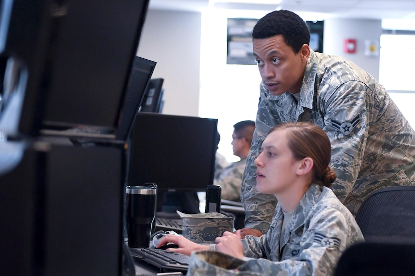 Two service members look at computer screens.