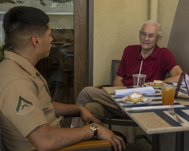 Lance Corporal Samuel Solislopez, a Due and Status File Clerk, I Marine Expeditionary Force Information Group, speaks about his experiences in the Marine Corps over lunch with Bob Casillas, a resident at The Covington, a retirement community in Viejo, Calif., October 4, 2017. This community outreach event also showed military veterans our support and appreciation for the sacrifices they have made.