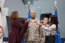 "Brig. Gen. Christopher ""Mookie"" Walker, Chief of Staff for the West Virginia Air National Guard, is pinned during his promotion ceremony by his sister, Nicole Walker, right, and family friend, Regina Evans, left, at the 167th Airlift Wing, Martinsburg, W.Va., Oct 14. (U.S. Air National Guard photo by Staff Sgt. Jodie Witmer)"