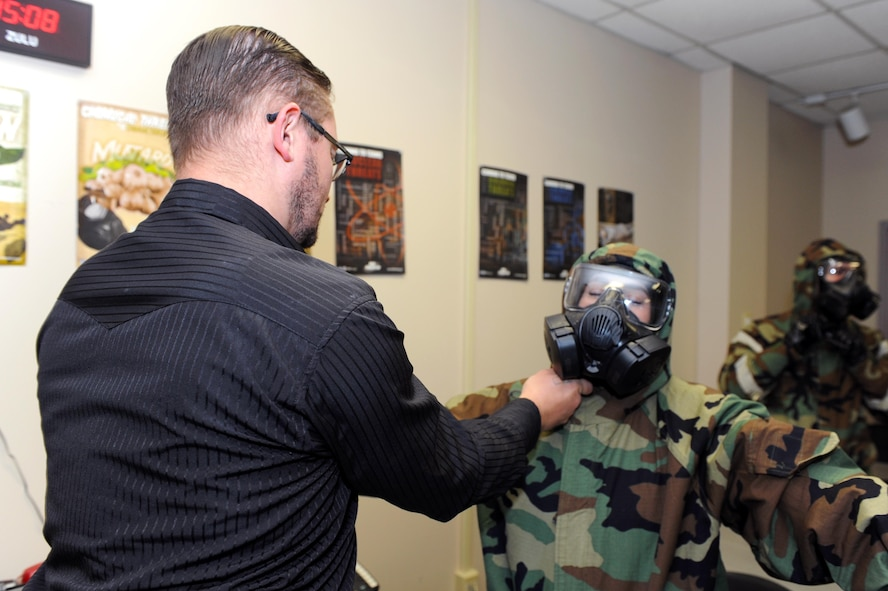 David Shore, 913th Force Support Squadron Chemical, Biological, Radiological, Nuclear and high-yield Explosives training instructor for the 19th Civil Engineer Squadron Readiness and Emergency Management flight, assists a student with her mission-oriented protective posture gear during CBRNE training Oct. 10, 2017, at little Rock Air Force Base, Ark. CBRNE training is intended to prepare Airmen for the possibility of a chemical, biological, radiological or nuclear attack. (U.S. Air Force photo by Airman 1st Class Grace Nichols)