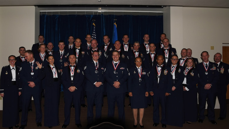 Col. Stacy Huser, 90th Missile Wing commander, and Chief Master Sgt. Kristian Farve, 90th MW command chief, pose for a photo with the bases newest senior non-commissioned officer corps inductees during a ceremony at the Trail's End Event Center on F.E. Warren Air Force Base, Wyo., Oct. 13, 2017. Some of the inductees already sewed on the rank of master sergeant, while the majority will promote over the next year. (U.S. Air Force photo by Braydon Williams)