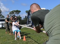 Maddison Niehus, daughter of Staff Sgt. Lisa Niehus, 81st Medical Group instructor, joins Keesler Marine Detachment Marines in a round of tug-of-war during Operation Hero Oct. 14, 2017, on Keesler Air Force Base, Mississippi. The event was designed to help children better understand what their parents do when they deploy. (U.S. Air Force photo by Kemberly Groue)