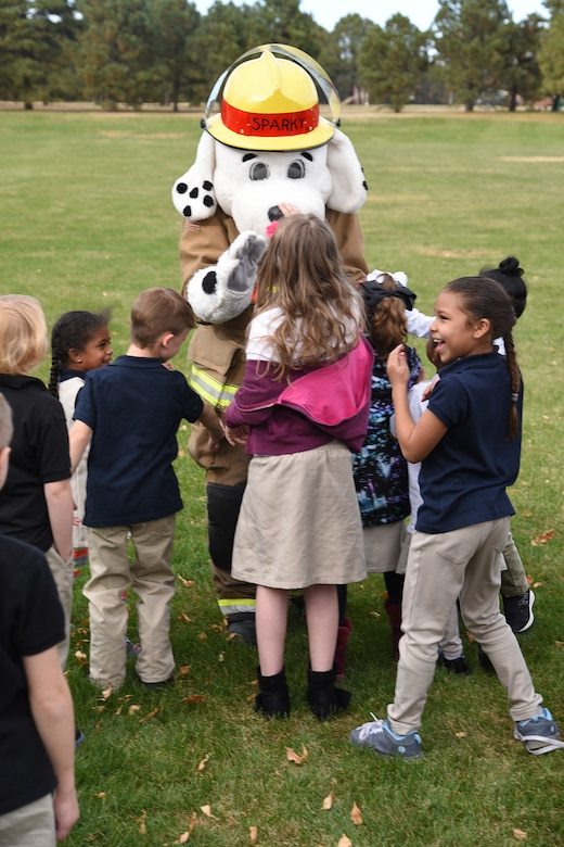 Sparky, 21st Civil Engineer Fire Department mascot, greets children behind the R.P. Lee youth center on Peterson Air Force Base, Colorado Oct. 11, 2017. He participated in a fire drill and evacuated the building with the children. (U.S. Air Force photo by Robb Lingley)
