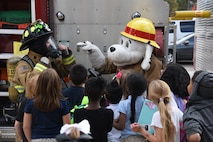 Sparky the mascot, and a 21st Civil Engineer fire fighter talk with children outside the Youth Center on Peterson Air Force Base, Colorado, Oct. 11, 2017. Sparky demonstrated an evacuation with the children during a fire drill. (U.S. Air Force photo by Robb Lingley)