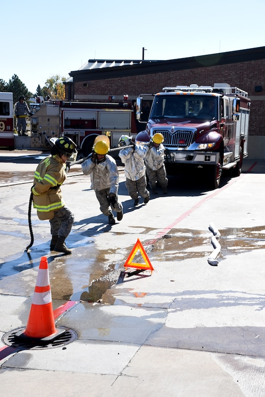 Four Airmen pull a fire truck to safety during the Fire Muster competition at the 21st Civil Engineer fire station at Peterson Air Force Base, Colorado, Oct. 13, 2017. Three teams of four Airmen competed in the event. (U.S. Air Force photo by Robb Lingley)